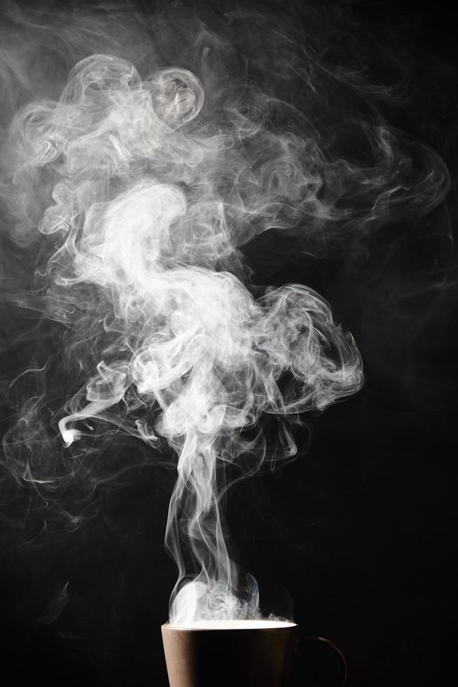 Dampf aus der Tasse auf schwarzem Hintergrund foto