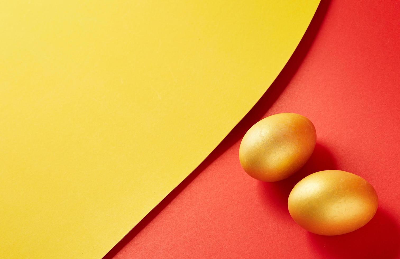 goldene Eier auf gelbem und rotem Hintergrund foto
