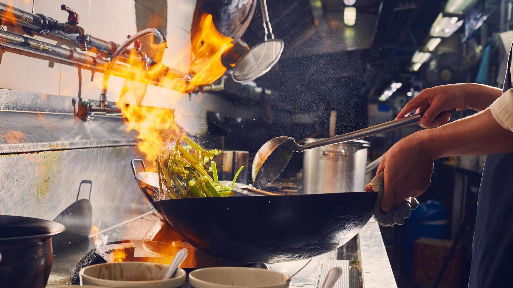 Kochen im Wok auf einem Herd foto