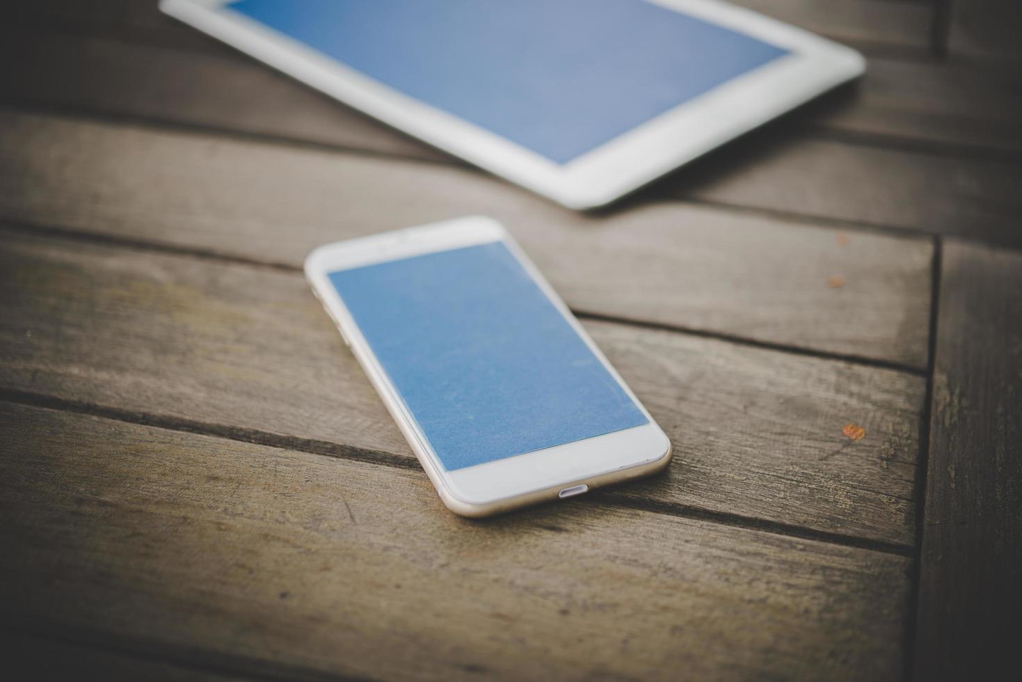 Smartphone und Tablet auf einem Holztisch foto