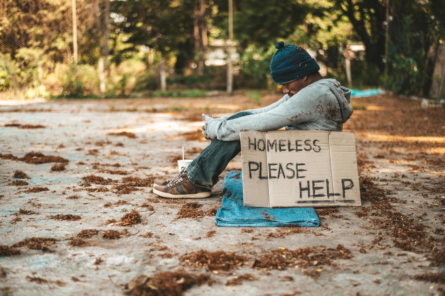Bettler, der mit obdachlosen Nachrichten auf der Straße sitzt, bitte helfen Sie foto