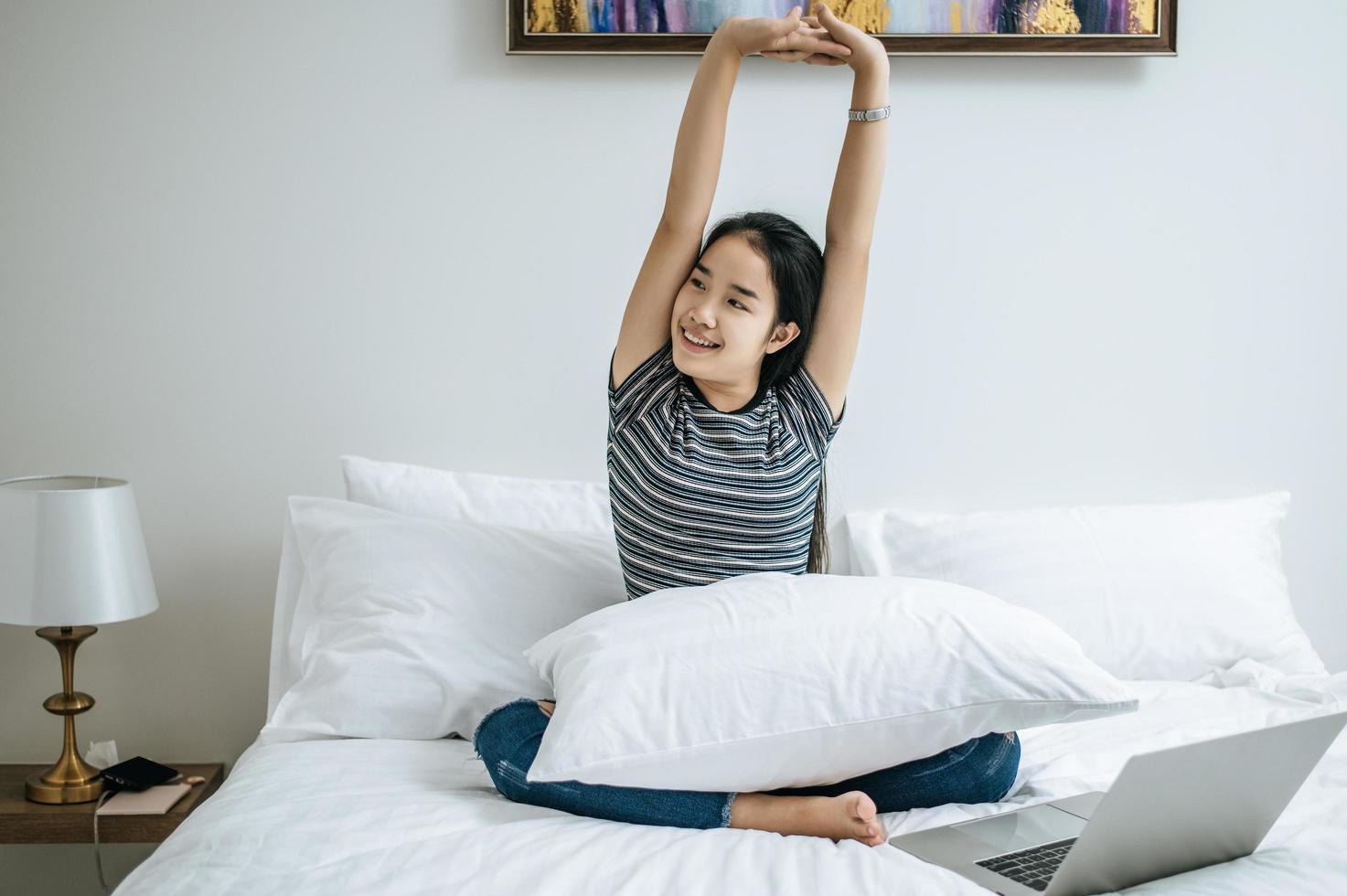 junge Frau sitzt auf ihrem Bett und streckt die Arme aus foto