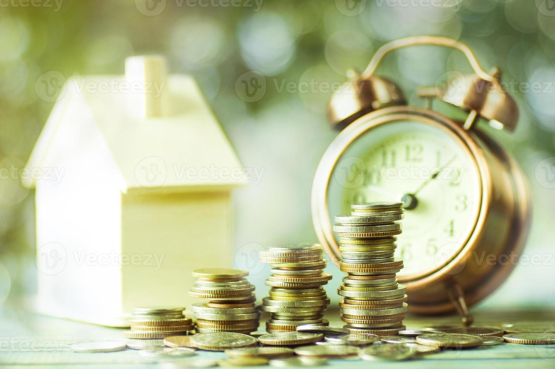 ein Stapel Münzen mit einem Musterhaus und einem Wecker foto