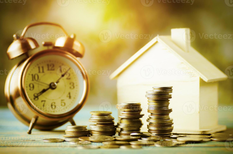 Stapel Münzen mit Modellhaus und Wecker foto