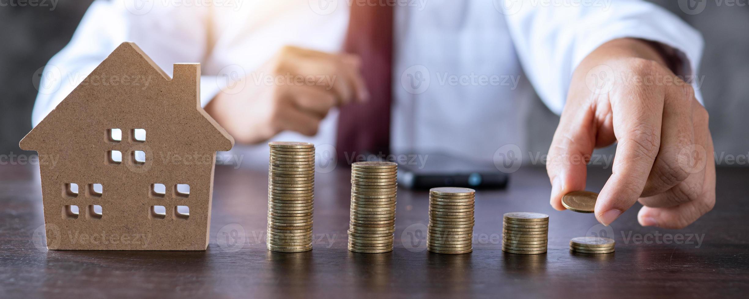 gestapelte Münzen mit Holzhaus foto