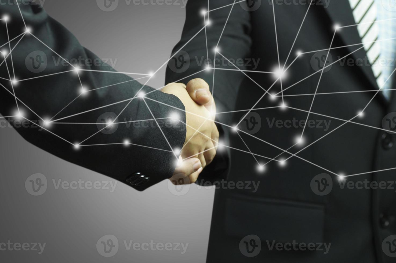 Geschäftsmann, der Hände auf grauem Hintergrund mit Verbindungsüberlagerung schüttelt foto