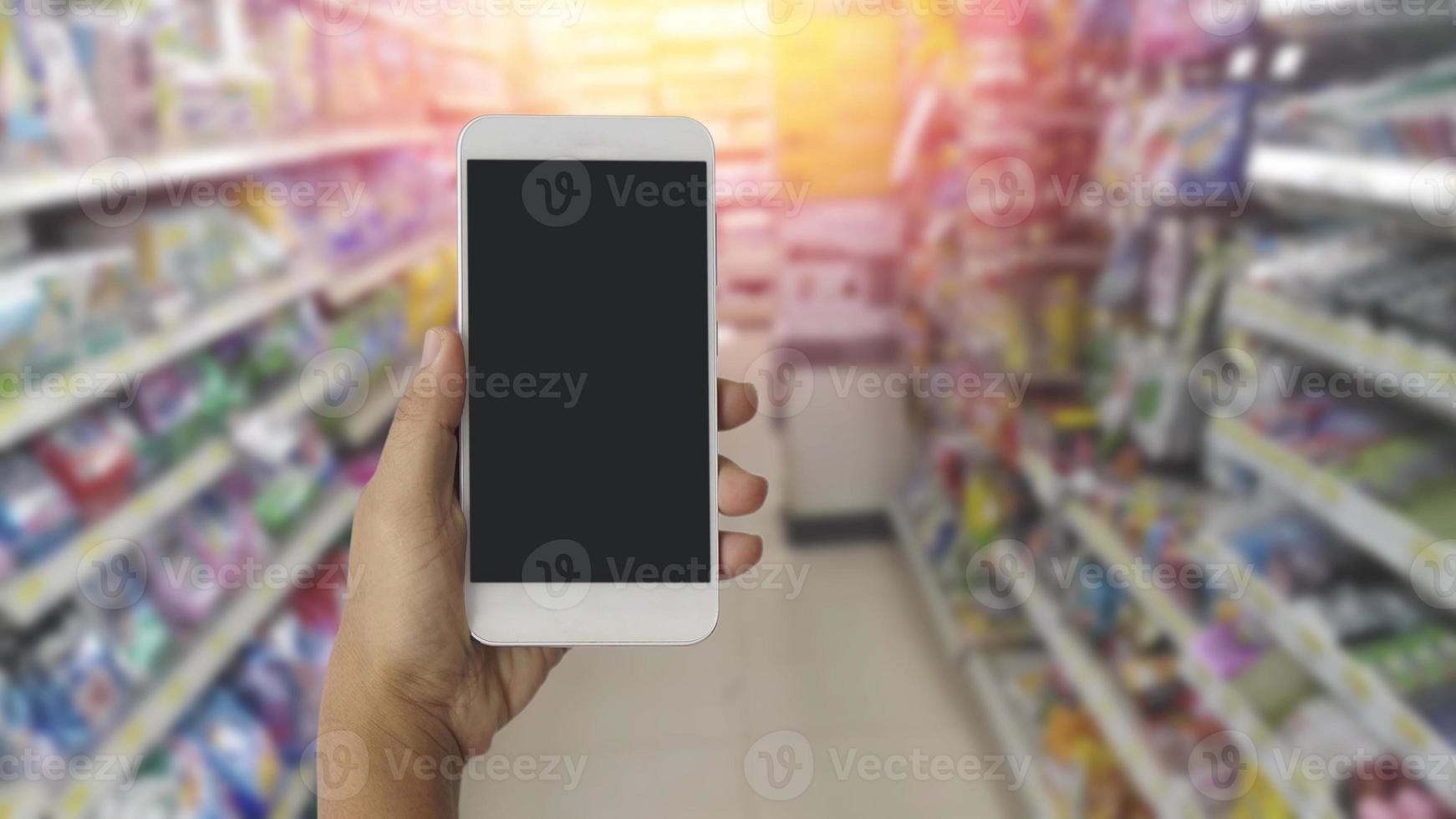 Hände mit leerem Bildschirm mobiles Smartphone mit unscharfem Hintergrund im Kaufhaus foto