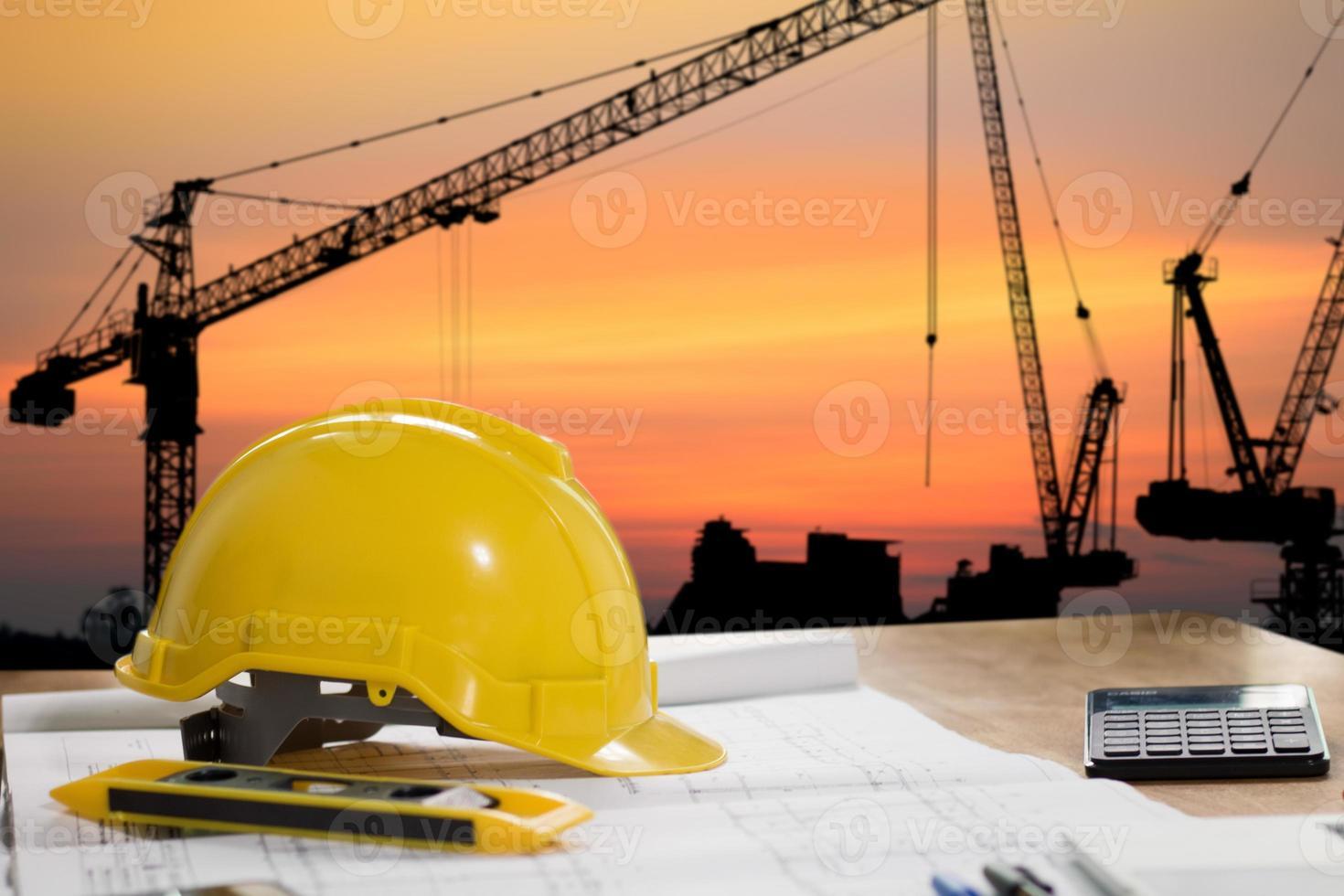 Schutzhelm mit Bauobjekten auf Tisch mit Stadtbild foto