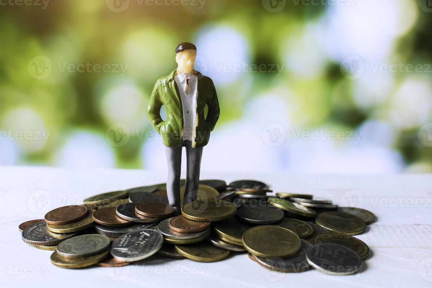 Geschäftsmann, der auf Geldmünzen steht foto