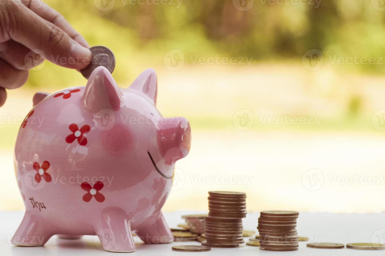 Geld in ein Sparschwein stecken foto