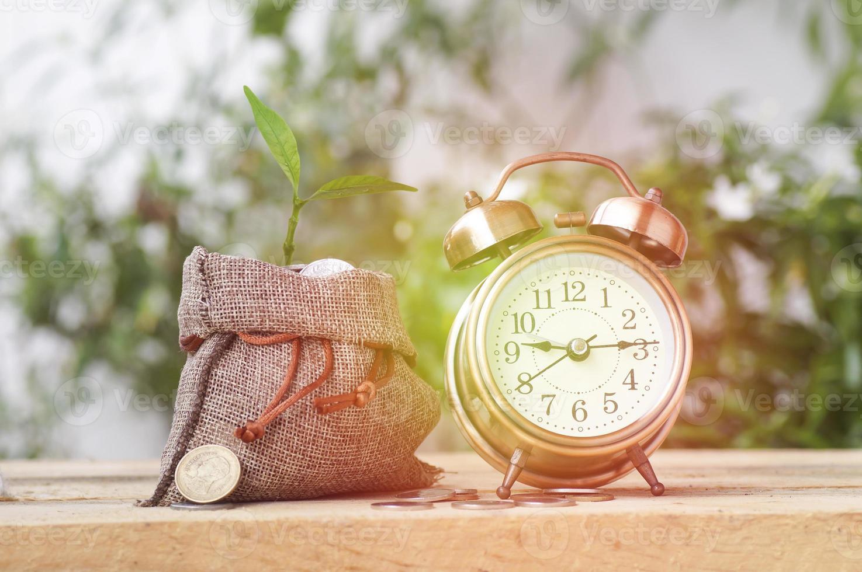 Wecker und ein Leinensack mit Pflanze darin foto