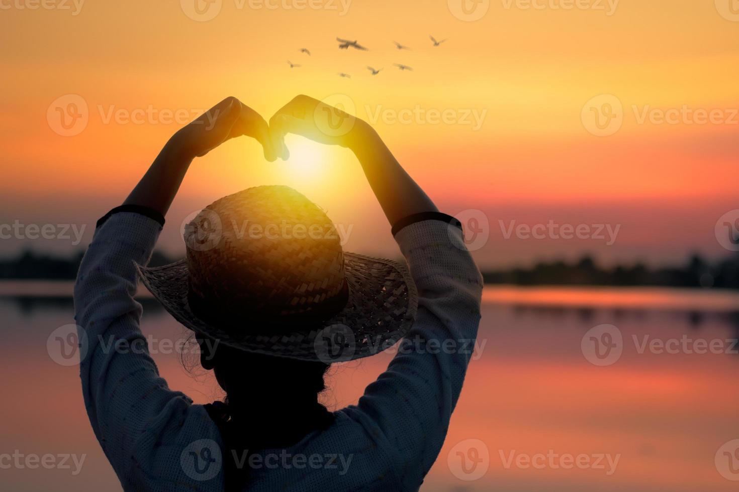 Liebe und glückliches Konzept, Silhouette der Frauen machen Herzform im Sonnenuntergang foto