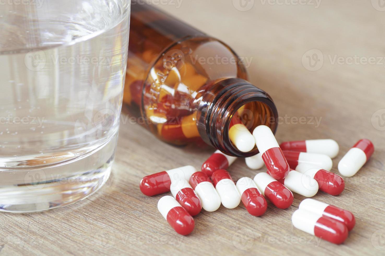 rote und weiße Pillenkapseln und Glas auf Flasche, die auf Holztisch gießt foto