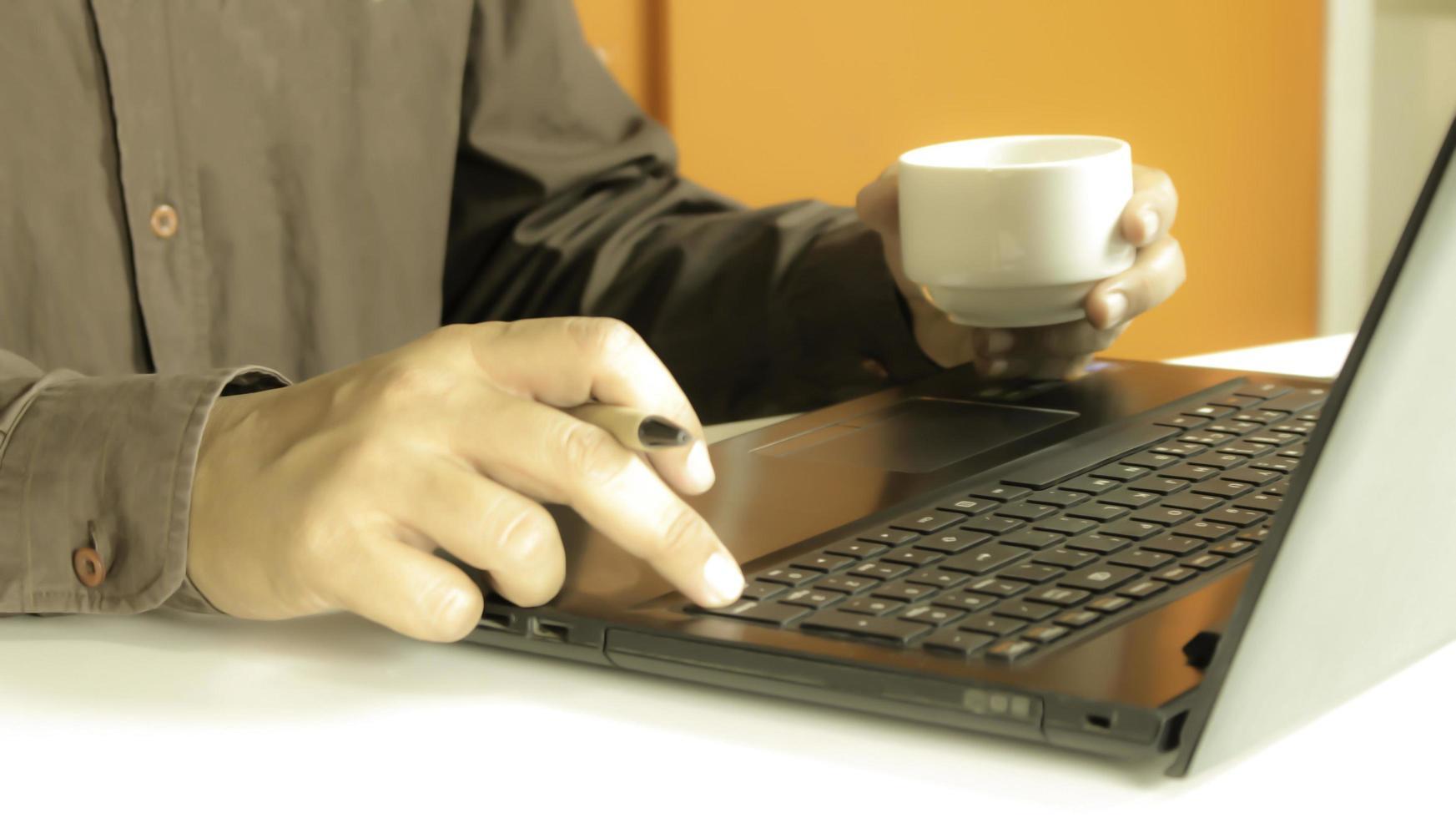 Profi arbeitet an einem Laptop und trinkt Kaffee foto