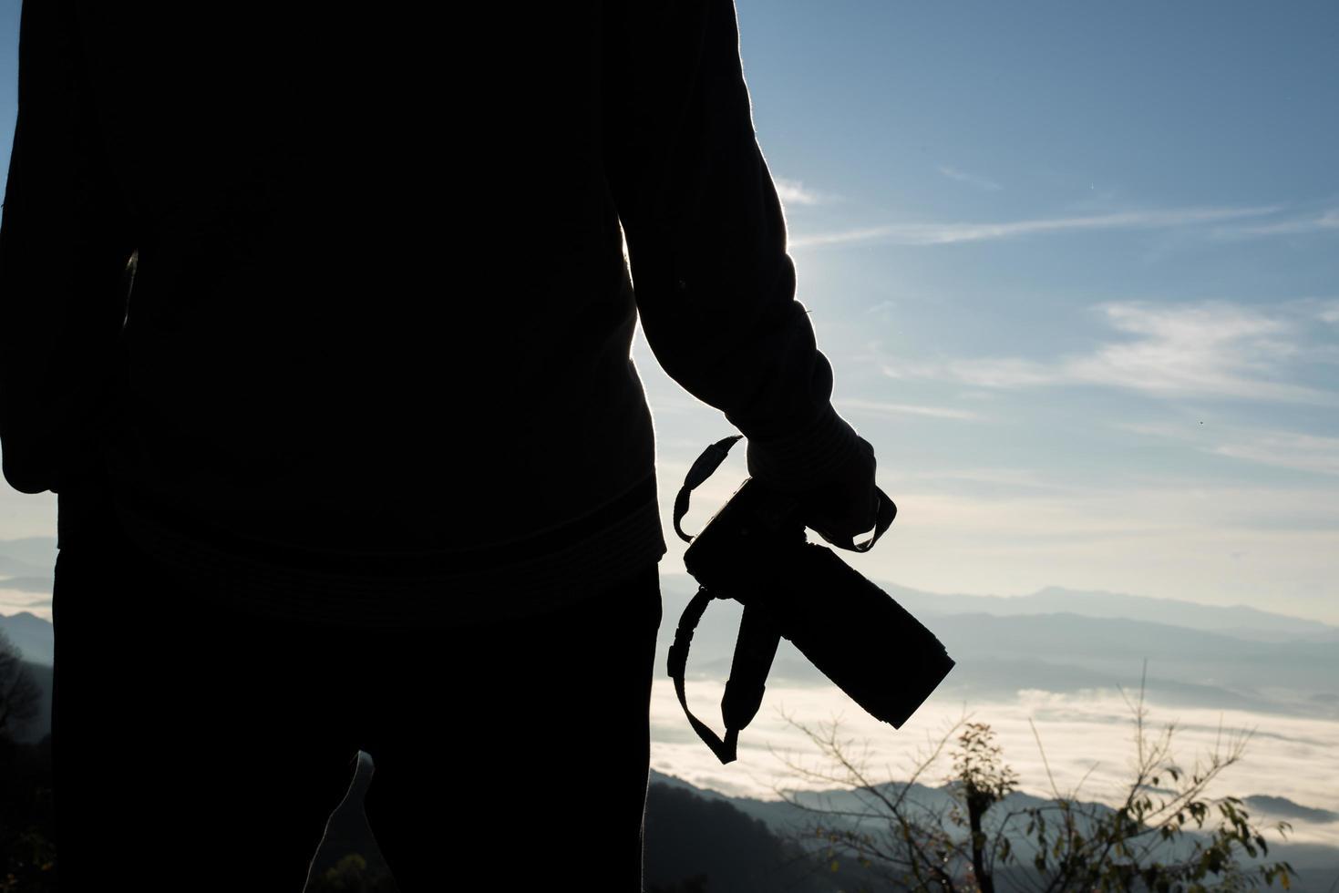 Schattenbild des jungen Fotografen, der eine Kamera mit Berglandschaft hält foto