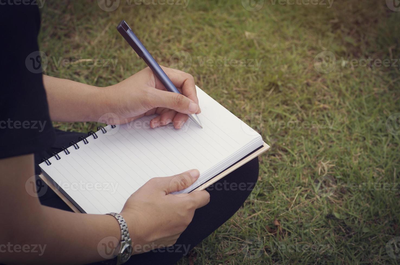 Person, die in ein Tagebuch schreibt foto