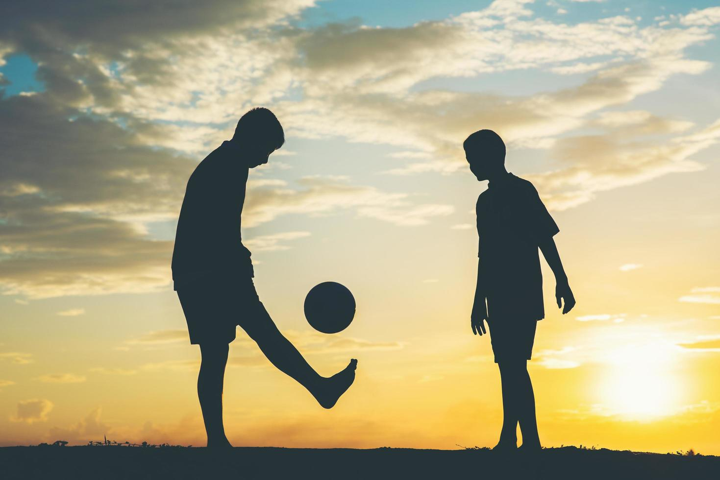 Silhouette von Kindern, die Fußball spielen foto