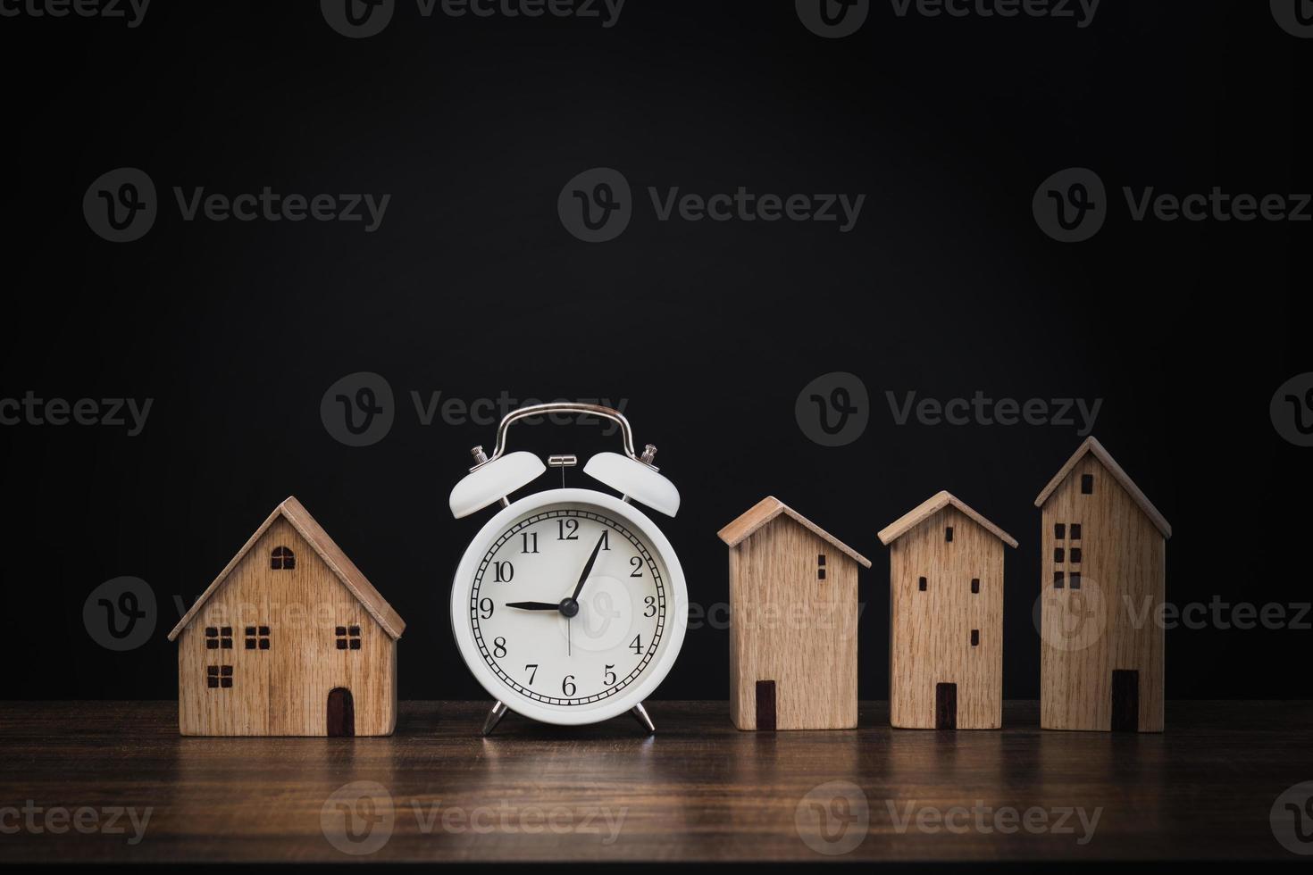Wecker mit kleinen Häusern auf schwarzem Hintergrund foto