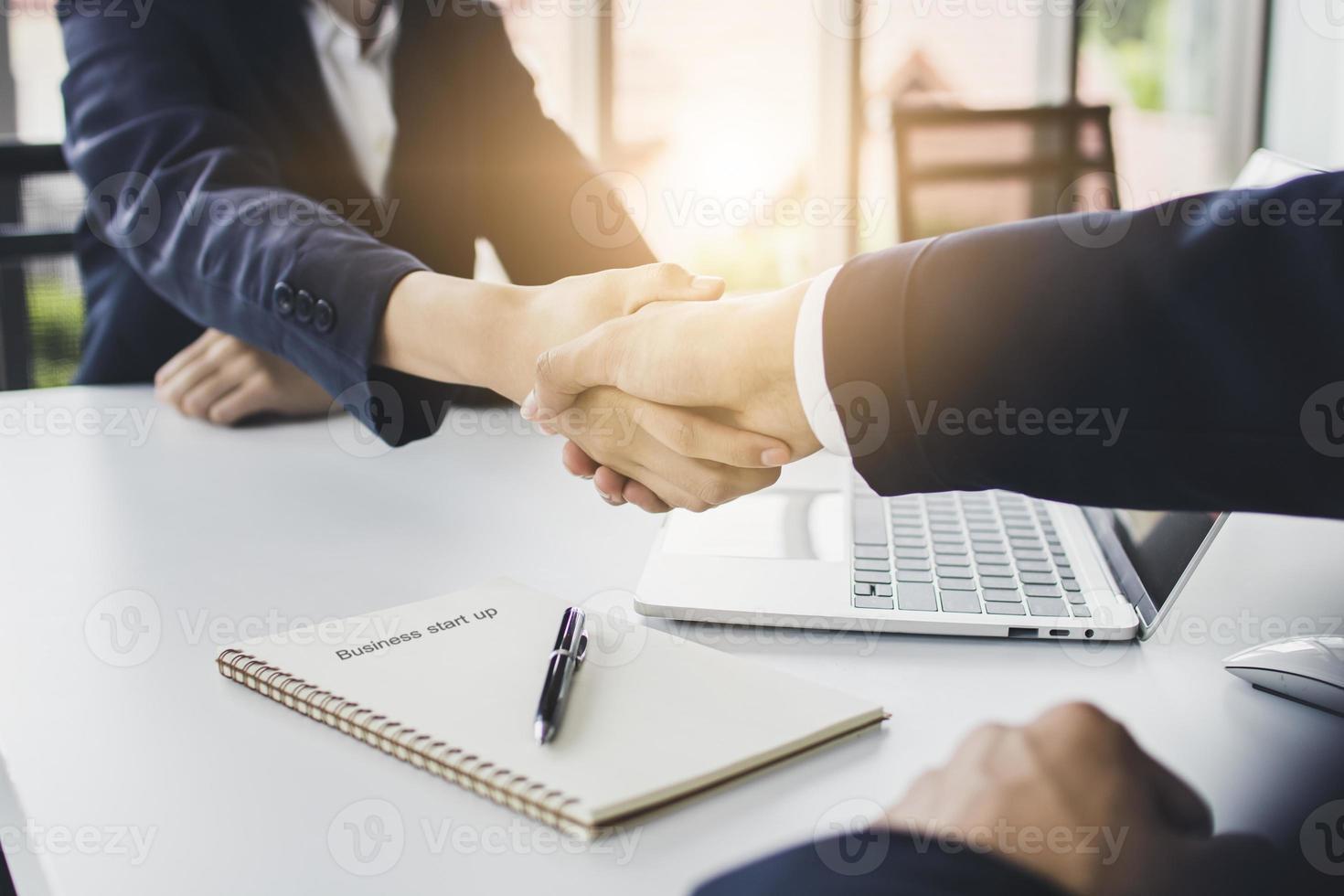 zwei Geschäftsleute, die sich die Hand geben foto