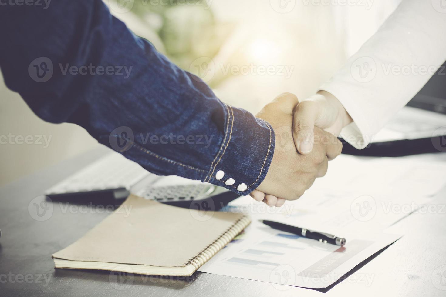 zwei Leute, die sich die Hand geben foto