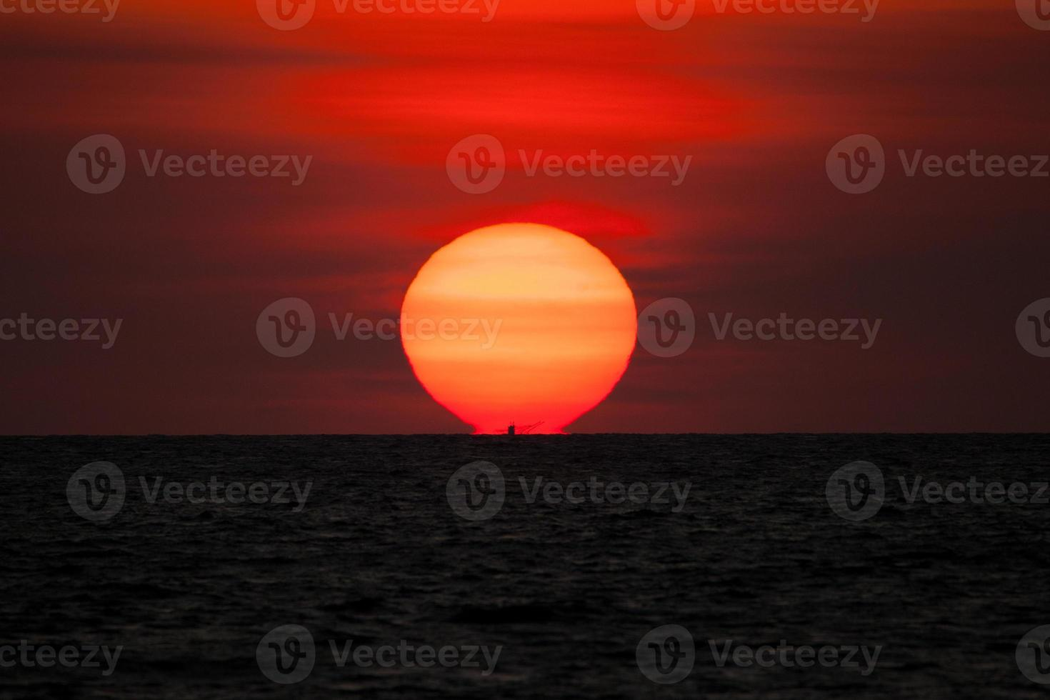 vergrößerte Sonne bei Sonnenuntergang foto