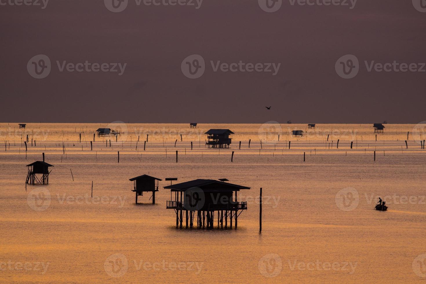 Silhouetten von schwimmenden Hütten bei Sunirse foto