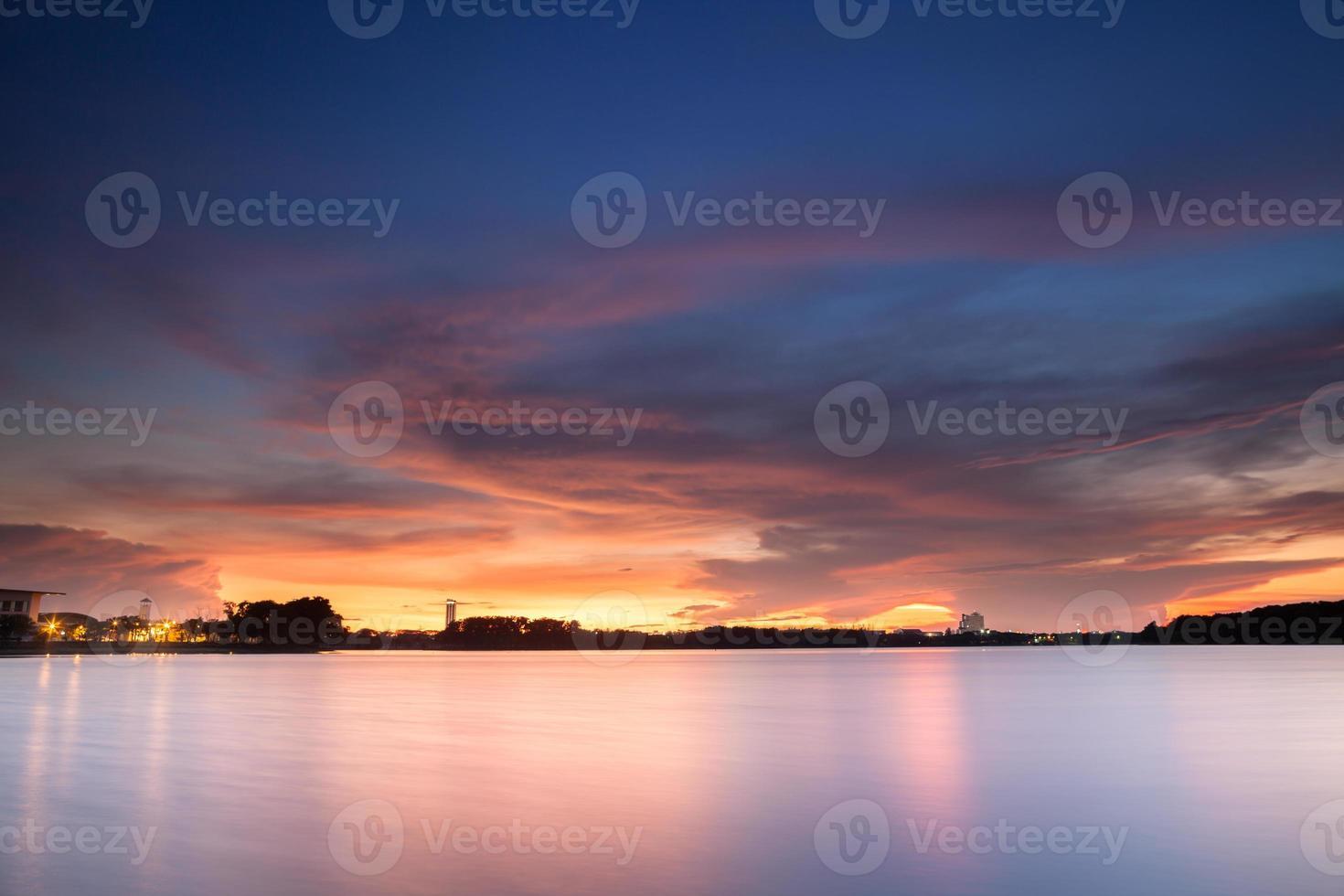 dramatischer Sonnenuntergangshimmel über Wasser foto