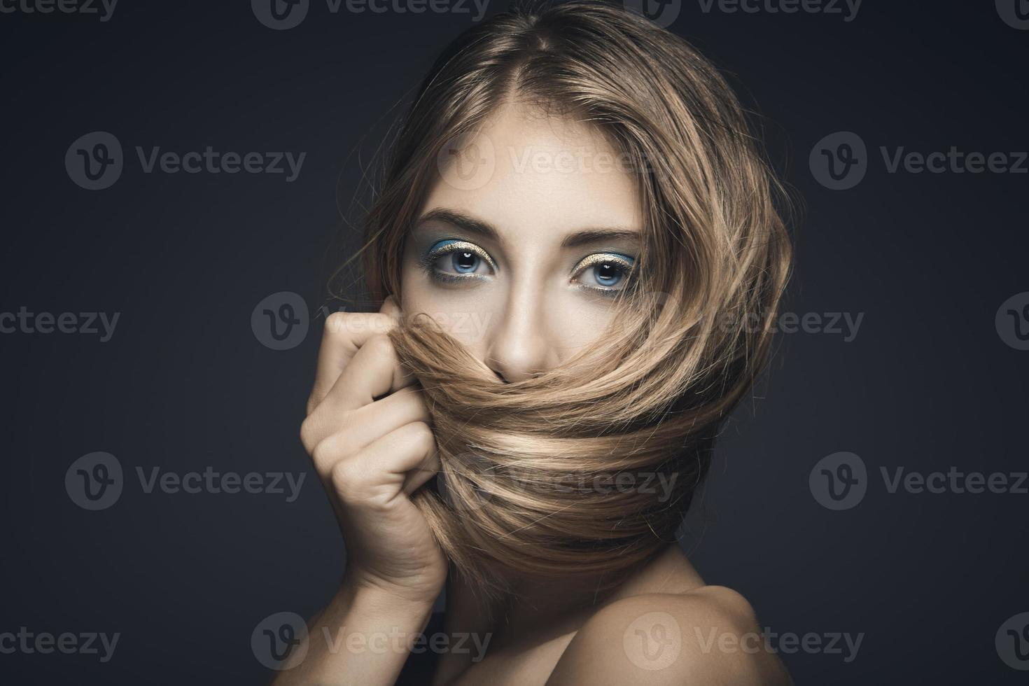 Schönheitsporträt einer jungen sexy Frau vor einem dunkelblauen Hintergrund foto