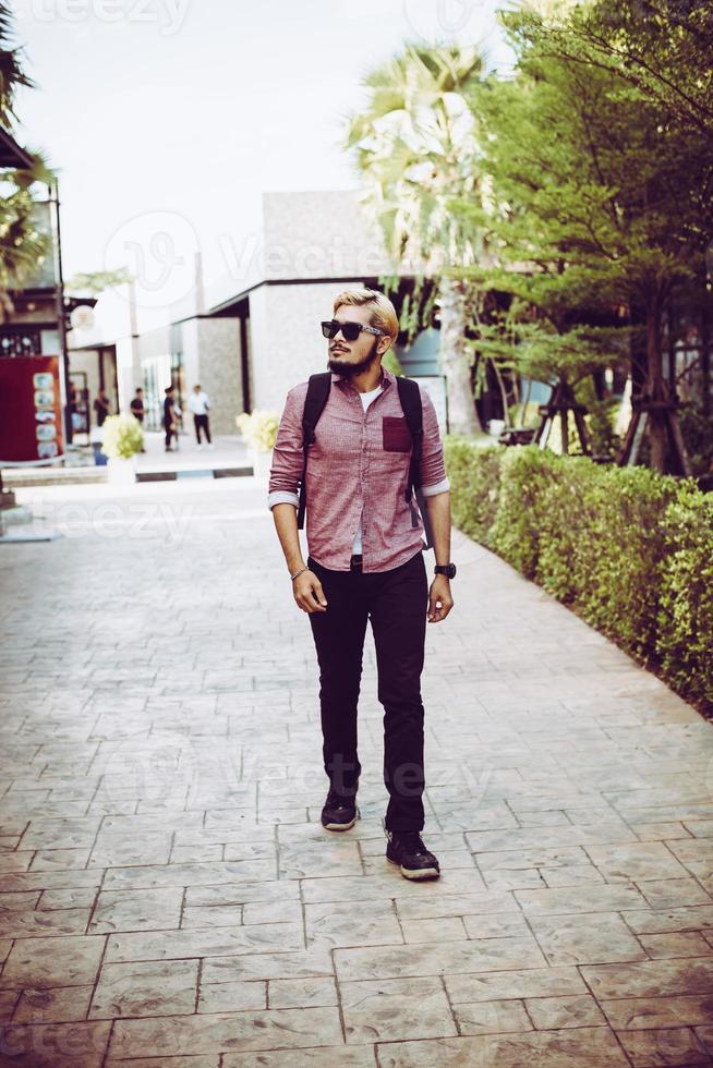 Porträt des hübschen Hipster-Mannes, der durch die Straße geht foto