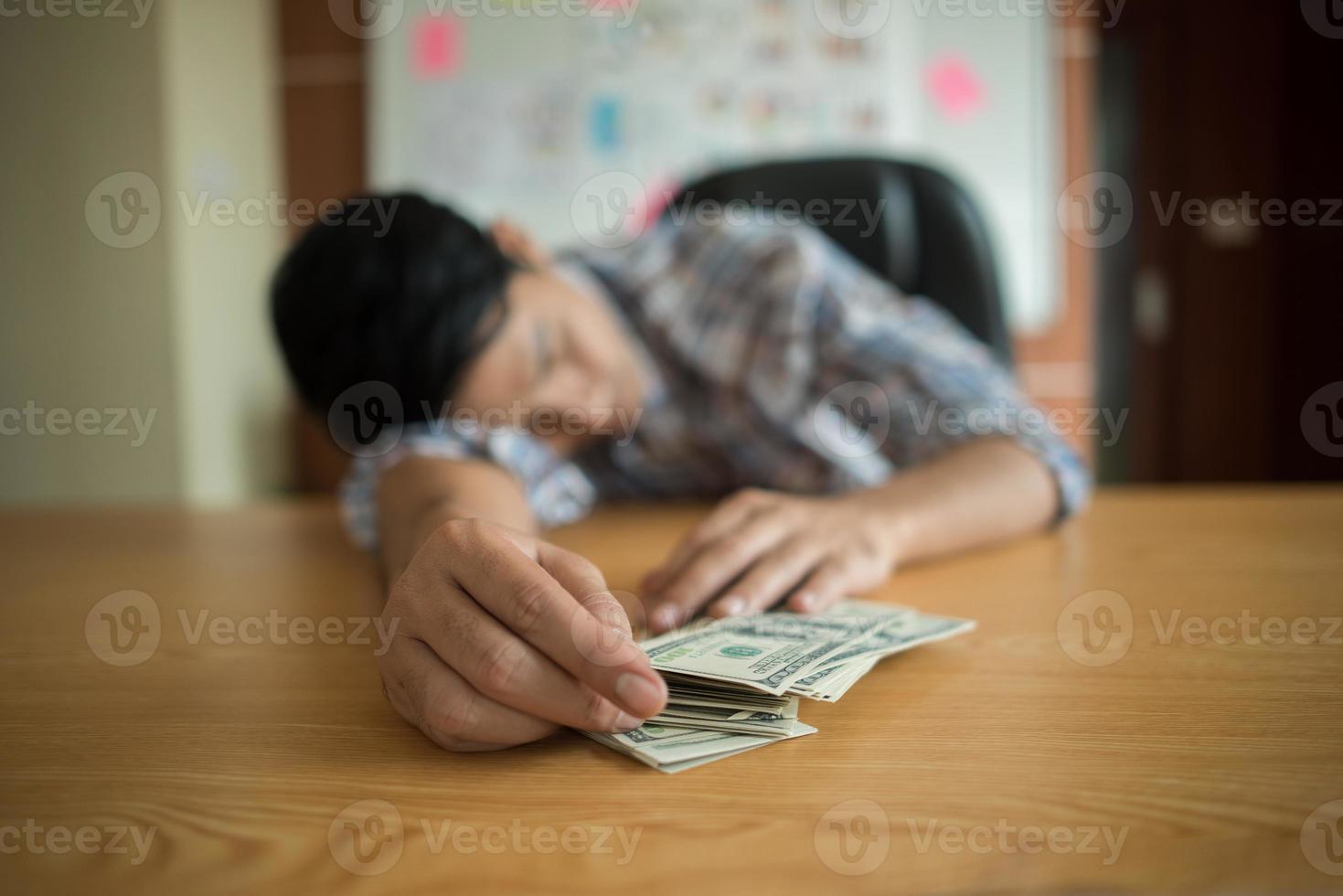 Mann schläft mit Dollarnoten foto