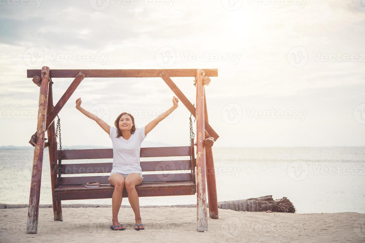 schöne Frau, die sich auf einer Schaukel am Strand ausdehnt foto