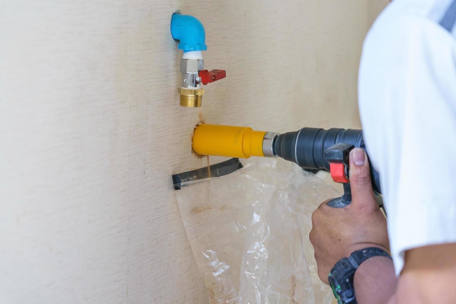 Arbeiter mit einem Bohrwerkzeug auf der Baustelle foto