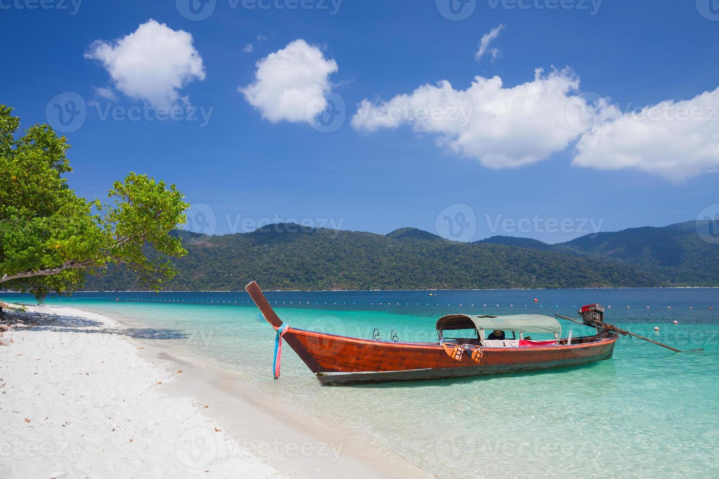 ein langes Boot an einem tropischen Strand foto