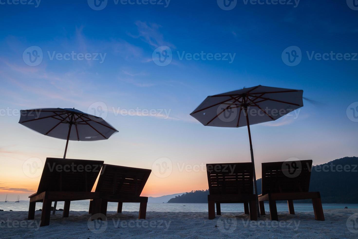 Silhouette von Stühlen und Sonnenschirmen bei Sonnenuntergang foto