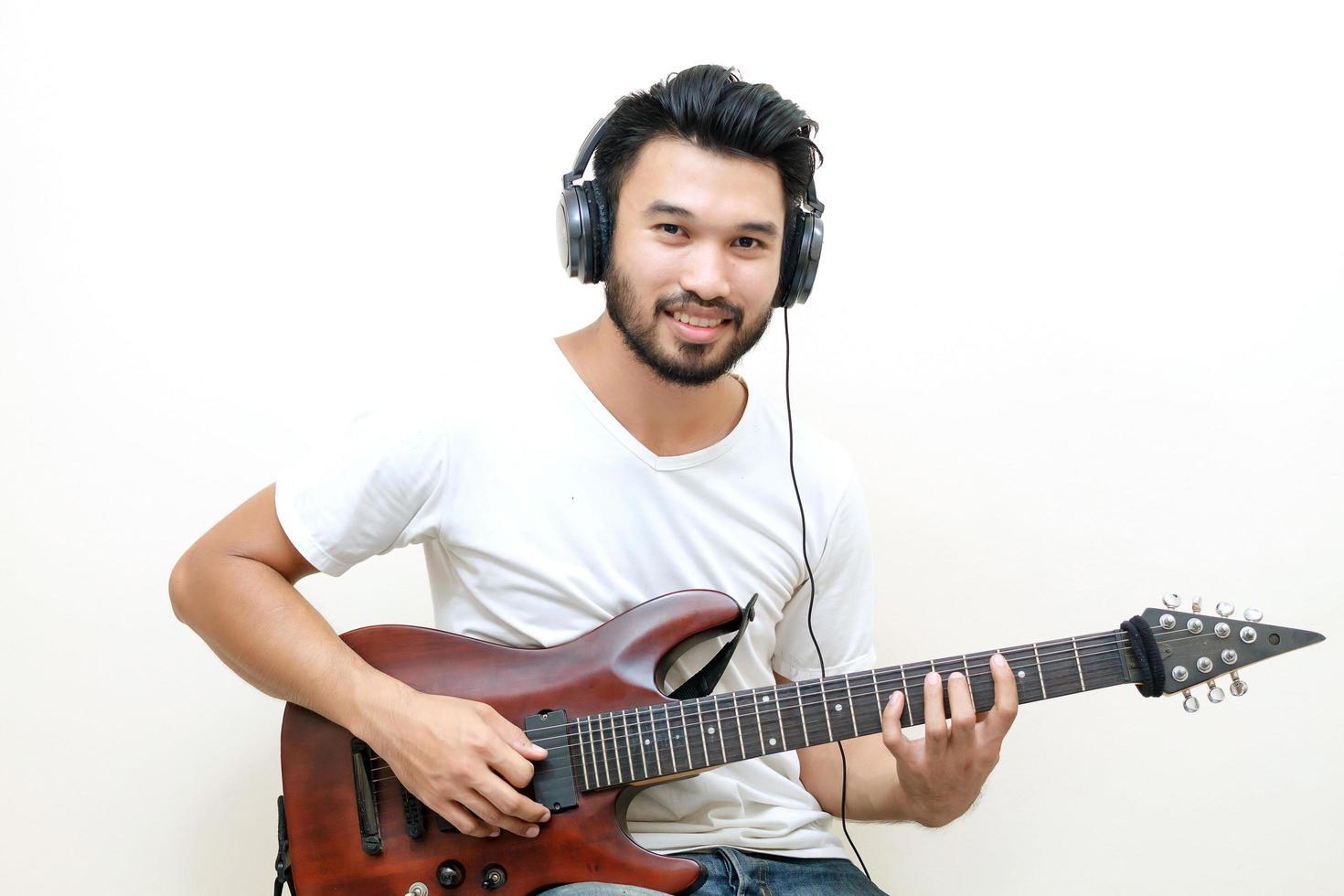 junger asiatischer Mann, der Gitarre spielt foto