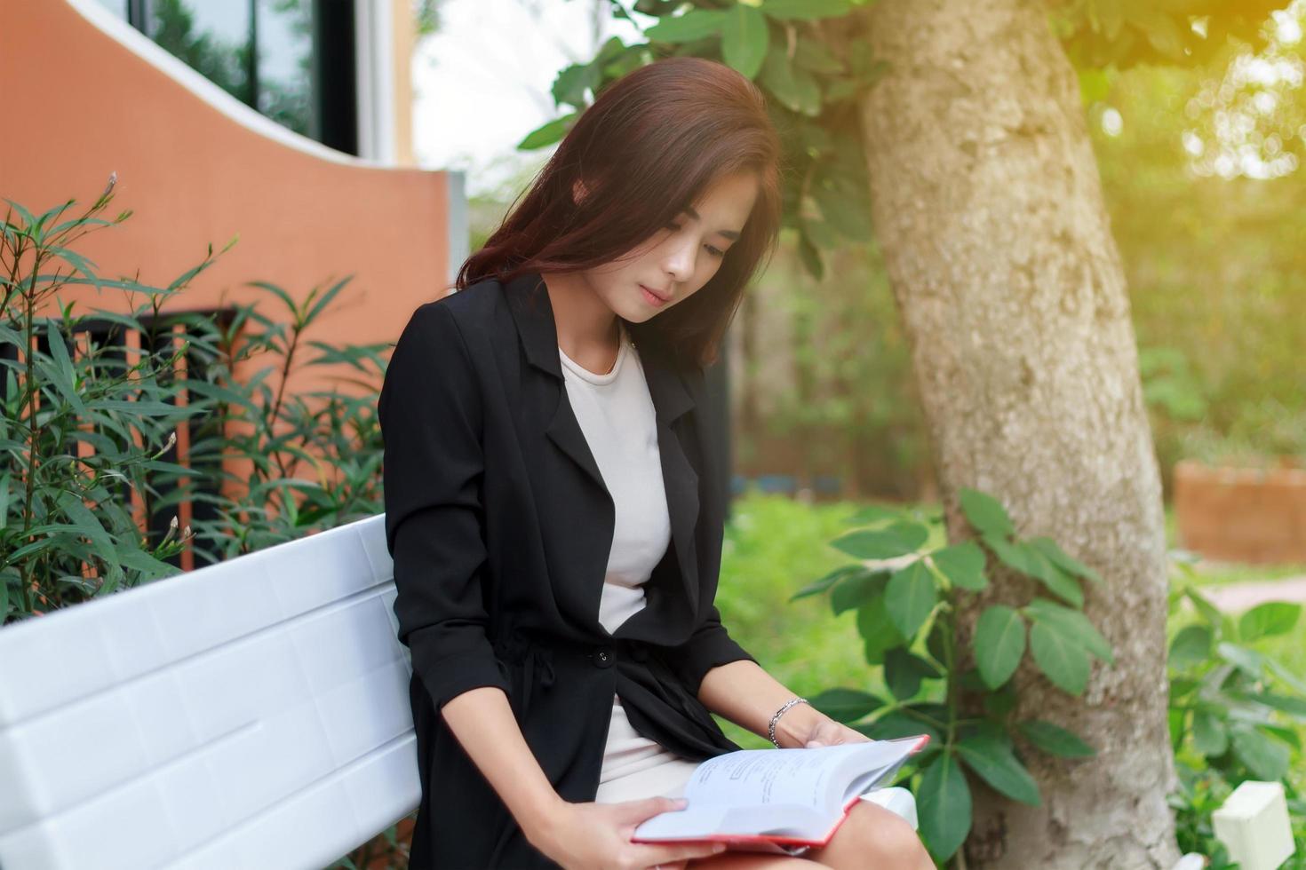 asiatische Frau, die draußen ein Buch liest foto
