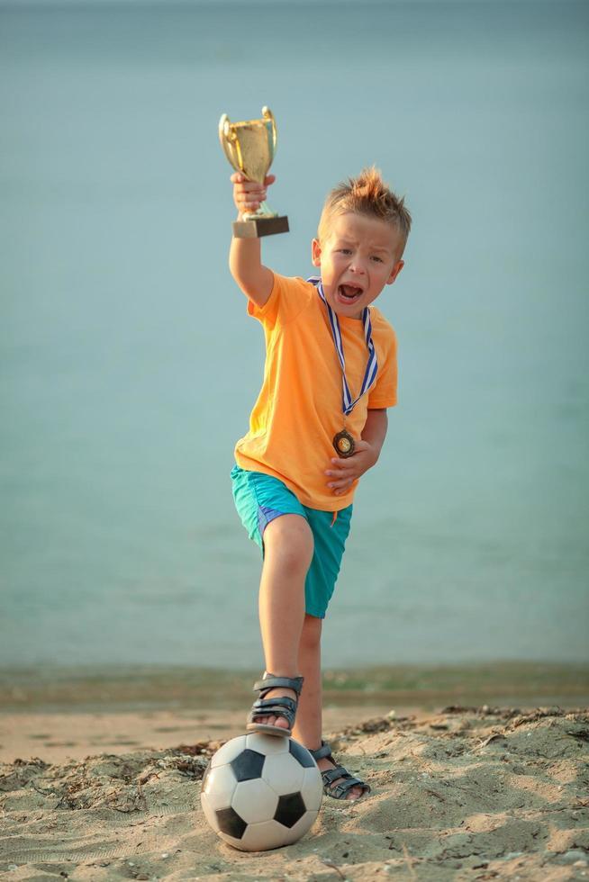 Junge posiert mit Trophäe und Fußball foto