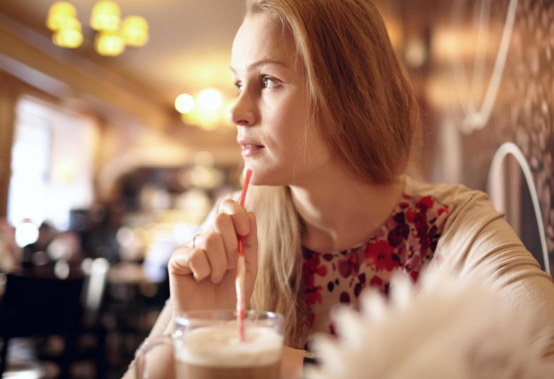 Frau hält einen Strohhalm und schaut weg foto