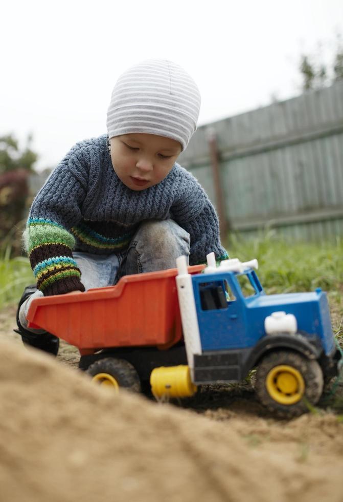 Junge spielt mit einem Spielzeuglastwagen draußen foto
