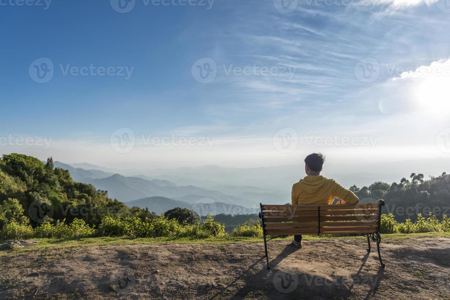 reisender Mann, der auf einer hölzernen Bank mit Bergen sitzt foto