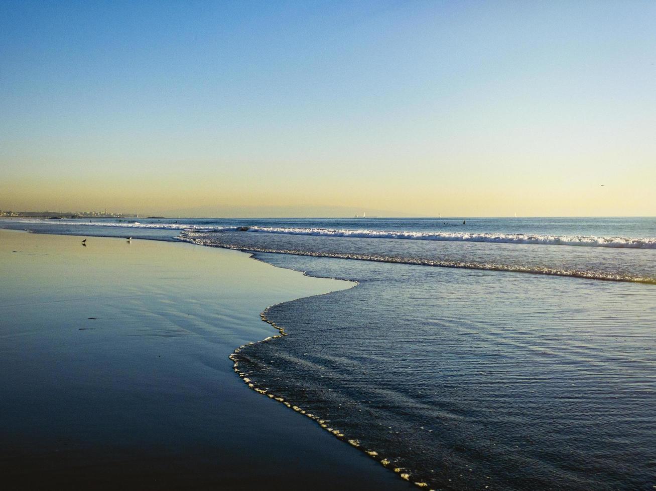 schaumige Wellen am Strand von Venedig während des Sonnenuntergangs foto