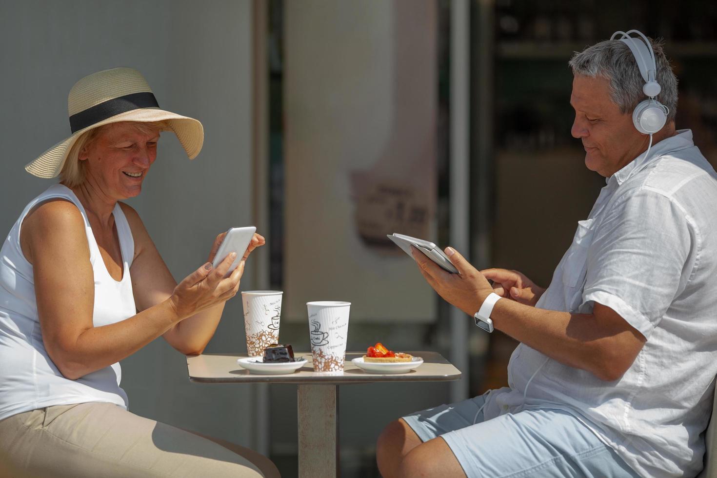 reifes Paar, das draußen mit Elektronik isst foto