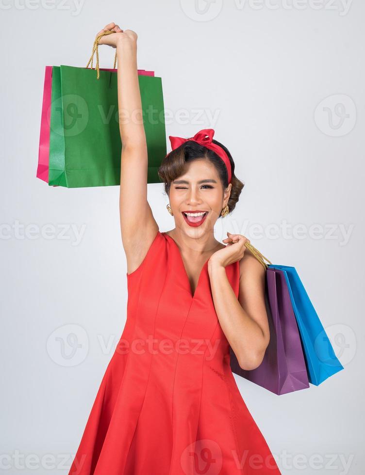 schöne asiatische Frau, die farbige Einkaufstaschen hält foto