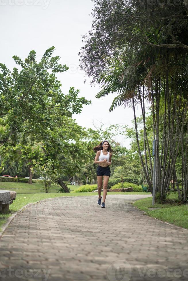 junge sportliche Frau, die am Park läuft foto