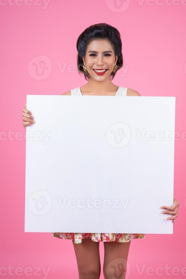 Porträt einer modischen Frau, die ein weißes Banner anzeigt foto
