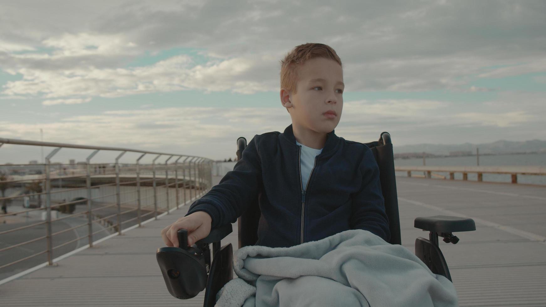 Junge im Rollstuhl draußen foto