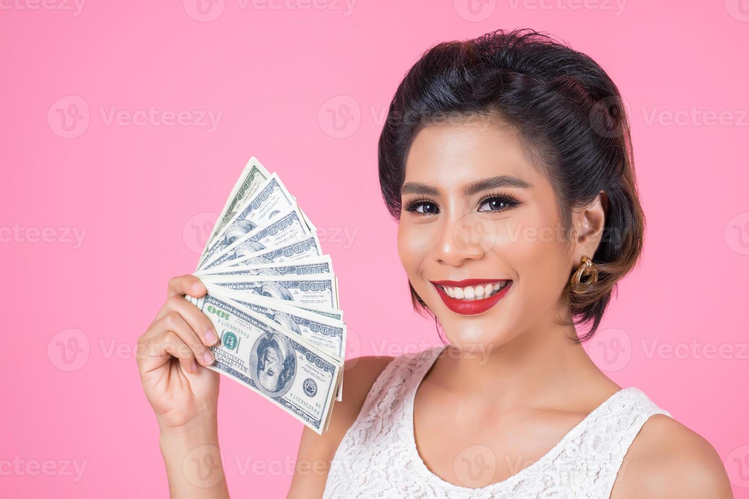 glückliche schöne Frau, die Dollars hält foto
