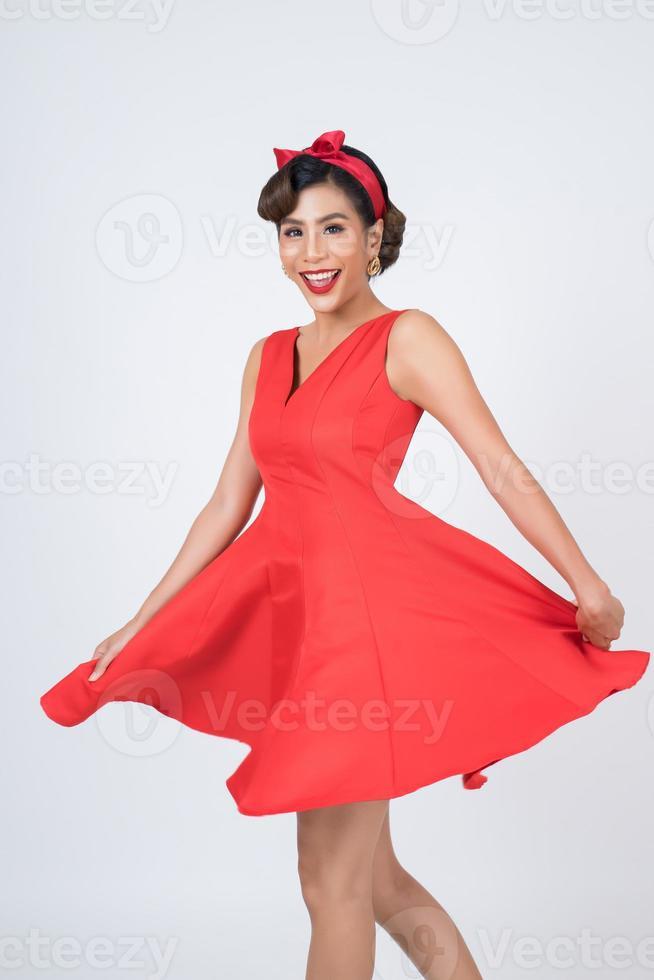 schöne Frau, die ein rotes Kleid im Studio trägt foto