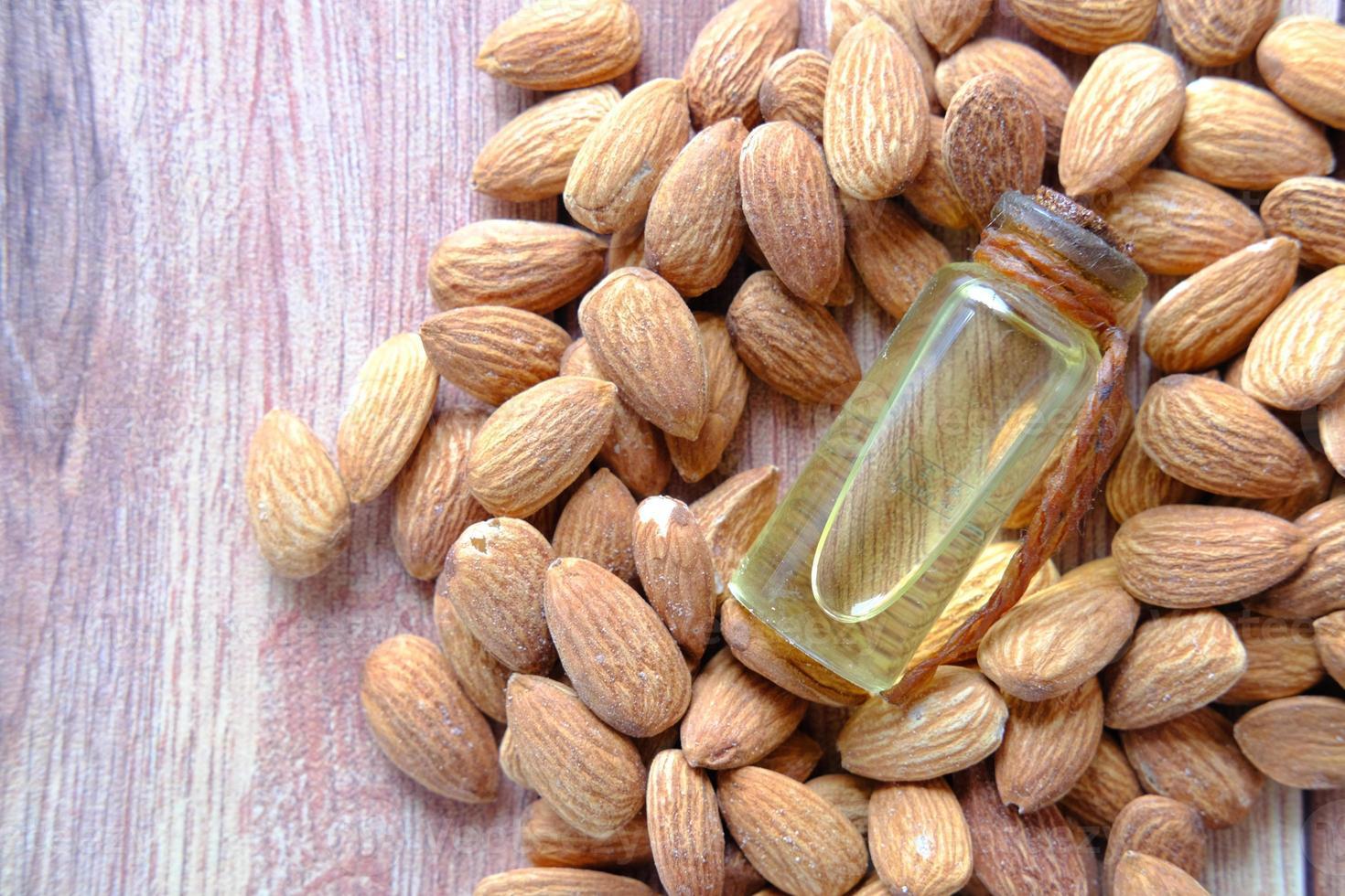 Mandelöl in der Flasche auf hölzernem Hintergrund foto