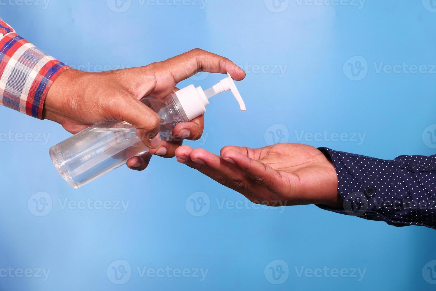 Hand einer Person, die einer anderen Person Desinfektionsflüssigkeit gibt foto